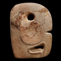 View 1: Ceremonial Hacha Representing a Macaw - Maya - The hooked beak is perforated in its centre. The nostrils are marked by a groove. A highlighted big circle that is decorated by two engraved feathers forms the eye. On top of the eye is a large circular hole, characteristic of the Mayan hachas. The top of the head is bulging and depicts the cutting edge of the hacha.