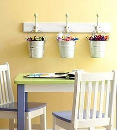 Creative crafting spot.  Using buckets to hold items.  Hang them up & they are out of the way!