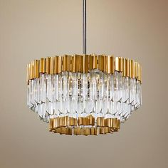 This Corbett pendant light is made up of tri-side crystal rods with gold leaf and polished stainless accents.