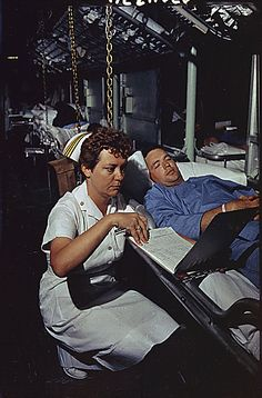 """""""Lieutenant Commander Dorothy Ryan checks the medical chart of Marine Corporal Roy Hadaway of Calera, Alabama aboard the hospital ship USS Repose off South Vietnam. Miss Ryan, from Bronx, New York, is one of 29 nurses aboard the hospital ship selected from 500 volunteers of the Navy Nurse Corps."""" 04/22/1966"""