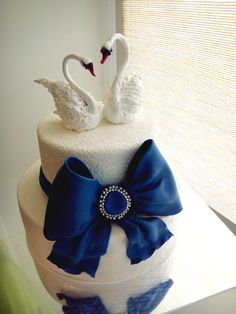 Свадебный торт с синим бантом и лебедями