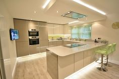 Kitchen Style – Acrylic Gloss Handless Kitchen in Ivory and Stone Grey. Quartz worktop, up-stands and window sill in Aluminio Nube. Serie 8 Bosch Appliances and a Falmec flat ceiling extracto…
