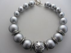 Three sizes of light grey pearls with a silvered large spacer bead in the middle. Striking statement necklace. Stylish and trendy!