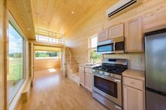 storage n stairs..daybed in livingroom.ESCAPE ONE XL: Beautiful 30' Zen Tiny House on Wheels