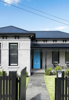 Facade: One of the core focuses of the renovation was restoring and re-introducing traditional details to the home. The grey rendered facade pairs beautifully with dark fencing and roofing, and a vibrant blue front door elevates the home's kerb appeal.