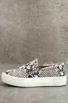"""There's nothing quite like the excitement of stepping out in your new Steve Madden Gills Natural Snake Slip-On Sneakers! Snake print embossed vegan leather shapes these cool girl-approved slip-on sneakers. Metal logo tag at the heel. 1.25"""" white bumper sole."""