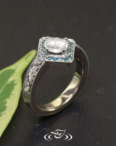 Custom 14kt palladium white gold halo style mounting oriented with 0.74ct round brilliant cut stone. Bead set in halo round cut teal blue diamonds and hand engraved scroll pattern down shoulders. - See more at: http://www.greenlakejewelry.com/gallery/gallery.aspx?p=1