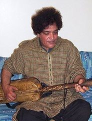 Famous Moroccan Gnawa Musician and Band member of Nass El Ghiwane,Maalem(Teacher) Abderrahmane Paco playing the hajhouj or guembri.