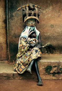 "Africa | ""Baba Ichanga"" wearing traditional gelede mask and holding a baby, evoking the ancestors, his generation and the most recent one. Sanga village, Ketou, Benin 