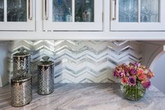 A bright, white kitchen with both traditional and modern elements and tons of details and a herringbone backsplash!