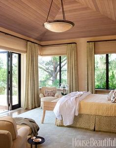 """Tree House Bedroom."" Wow, where can I buy a house with a master bedroom like this? ""Designer Suzanne Tucker created this country house in California. A ceiling of natural cedar brings the outdoors in and creates texture and warmth in the master bedroom. The silk and linen Stark rug adds plush softness. Curtains and bed skirt are Leopard by Raoul Textiles. Dome pendant light from Hilliard."""