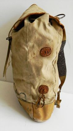Rugged Vintage Leather and Canvas Backpack. Very nice thick leather base with heavy duty khaki canvas body. Thick leather backpack adjustable straps with wool padding. Drawstring closure with deer antler pull tab. Heavy duty buckles and D ring. Inside has canvas sectioning for organizing items. Measures 20 tall, 14 across and 5.5 deep.