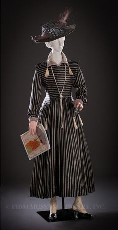 Circa 1916 Day Dress by Harvey Nichols, London, England. Printed silk, cotton organdy, and cotton floss.  Hat is from J.W. Robinson Co., Los Angeles, California, circa 1917.  Metal sequins, silk velvet, and dyed and lacquered stripped ostrich feathers.