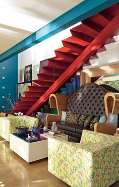 O interior da casa do arquiteto Leo Romano é marcado pela mistura de cores primárias. A escada metálica é vermelha. Sob ela, fica o sofá criado pelo profissional e poltronas de Jorge Zalszupin