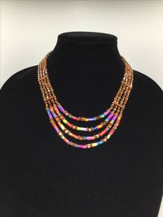 Handmade four-strand paper bead necklace accented with copper and Czech glass beads.