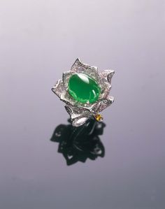 Samuel Kung showcases this almost translucent Imperial green cabochon jadeite stone by setting it in a diamond flower ring.