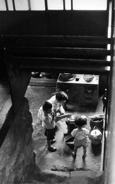 Kamado / Furnace, 1957. Mother with children cooking at electric kettle