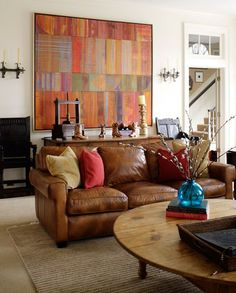 Coordinate your wall art with a leather couch by adding solid colored pillows | Suellen Gregory