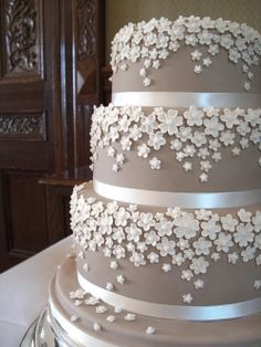 Three tiered wedding cake decorated with delicate white flowers, from Jo