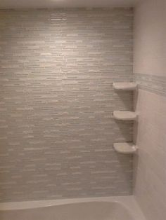 Gray tile feature wall in shower with built-in shelves.