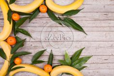 Wood background with bananas and tangerines frame.