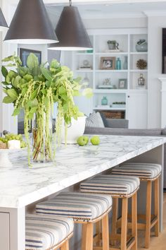 A Modern Farmhouse bright white kitchen with a carrara marble oversized island. The gray on the island is Galveston Gray by Benjamin Moore. Barstools are custom made with a blue striped fabric. Project Newport Harbor - Blackband Design