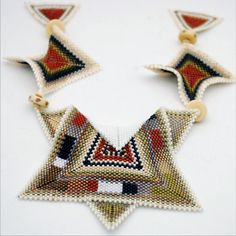 4 triangles sewn together makes the floppy squares. focal looks like 2 different triangles layered but how is that white section done? Seed Bead Jewelry, Seed Beads, Beaded Jewelry, Handmade Jewelry, Jewellery, Geometric Necklace, Geometric Jewelry, Peyote Stitch Patterns, Beading Patterns