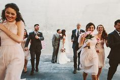 Awesome wedding photo idea -- the wedding party leaving while the bride and groom kiss!