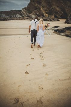 Bride & Groom walking in the sand - Image by Ali Paul Photography - Bohemian wedding dress from Grace loves Lace at a laid back coastal beach wedding in Cornwall. Bridesmaids wear duck egg blue dresses from H&M and groomsmen wear jeans, flip flops and braces.