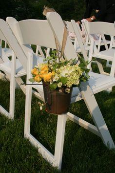 rustic aisle decor of yellow spray roses, mini green hydrangea, geranium, mint and dogwood in galvanized metal buckets tied with burlap ribbon
