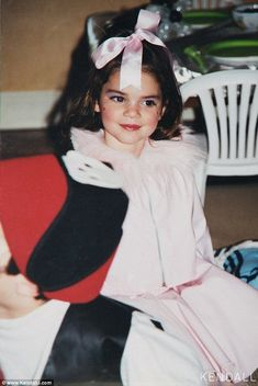 'I was totally dolled up!' Kendall Jenner celebrated Throwback Thursday by sharing a snap of herself as a tyke in full make-up and wrapped with a pink bow #kendalljenneroutfits