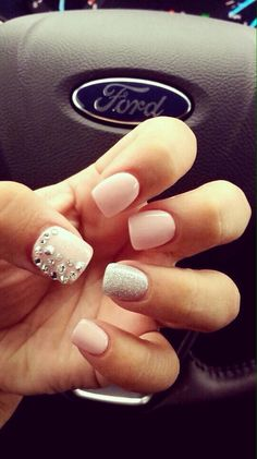 Pink nails with one finger with sparkles and the lumb with little rune stones
