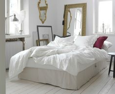 A light living room with a beige sofa-bed converted into a bed for two with white bedlinen.