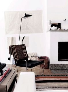 fauteuil noir design et déco de coin de lecture avec cheminée