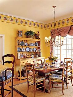 Country French style breakfast room. The yellow plaid wallpaper adds to the area's warmth along w/  a border featuring a series of plates with a floral motif. A rustic pine hutch for display and storage.