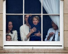 Prince George, who is expected on the blacony of Buckingham Palace later today in his first official appearance on British soil, is pictured smiling at the windows of Buckingham Palace today as the traditional Trooping the Colour parade takes place outside
