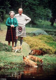 Queen Elizabeth wearing a tartan skirt holding a walking stick with corgis beside her and Prince Philip wearing kilt at Balmoral in 1994