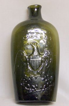 "BOTTLE G11-62 LIBERTY / EAGLE over Laurel branches Willington Glass Co., West Willington, CT Ca. 1840s Pint.  Emerald green. Sheared lip, open pontil (off-center) Crudely blown with lots of bubbles. Condition: perfect. Size: 7 ¼"" high."