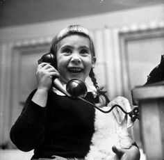 A young girl talks to Santa Claus on the telephone, 1947.