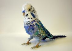 Blue Budgie by Karen Suzuki.  Karen creates animals from mixed textiles, building up new, complex fabrics from existing new and recycled textiles. She uses the qualities of each fabric – ripped edges, fraying, stretching, opacity or transparency, as well as their colour, pattern and textural qualities – in combination with exposed, expressive hand stitching in a manner like drawing, finding the form through needle, thread and scissors.☆