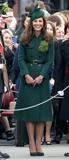 Catherine, Duchess of Cambridge, aka Kate Middleton, at the St. Patrick's Day parade with the Irish Guards. She is wearing a rayon/wool blend trench coat by Hobbs called the 'Persephone,' her green Gina Foster hat, new Emmy pumps and clutch, with her Kiki McDonough cushion cut green amethyst earrings and Tissot watch. Kate's jewelry today also included the Cartier shamrock brooch first worn by Queen Alexandra in 1901 when she visited the Guards. 03/17/14