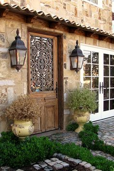 Charming stone cottage with ornate door and lanterns. ~ Balboa Island, California  Love the lanterns and the beautiful door.