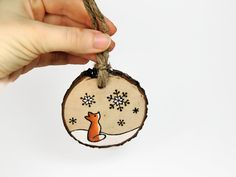 I wood burned the little fox design by hand on a slice of dogwood branch. I then filled in the design with professional quality acrylic paint,