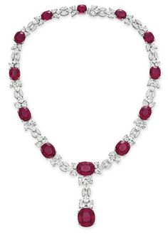 A RUBELLITE TOURMALINE, DIAMOND AND COLORLESS SAPPHIRE NECKLACE Designed as a graduated series of oval-cut rubellite tourmalines, each flanked on either side by three pear-shaped colorless sapphires, spaced by circular-cut diamond navette-shaped links, suspending an oval-cut rubellite tourmaline pendant of similar design, mounted in 18k white gold, 17 ins.