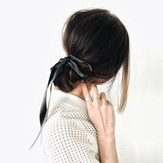 Low ponytail with an undone black satin bow
