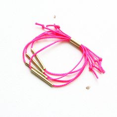 NEON STRANDS BRACELET / stacking bracelet featuring handmade brass beads strung on vibrant neon pink cord with tube closure
