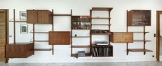 A Poul Cadovius wall units system in teak from the 1960s. Three vertical ladders with seven shelves, one container with sliding glass doors, one container with a flap and the last one with several compartiments for books or disks. Danish modern Poul Cadovius Royal System design (1965). Good condition with small traces of usage.The length of all units is standard: 80 cm.Three size shelves : D. 22, 30 and 38 cm. 2 boxes of identical size : H. 42,5 cm, D. 38 cm and the third one : H. 65 cm, D…