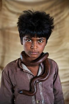 Intense eyes of a boy from India with a snake around his neck -  (Photo by Steve McCurry)
