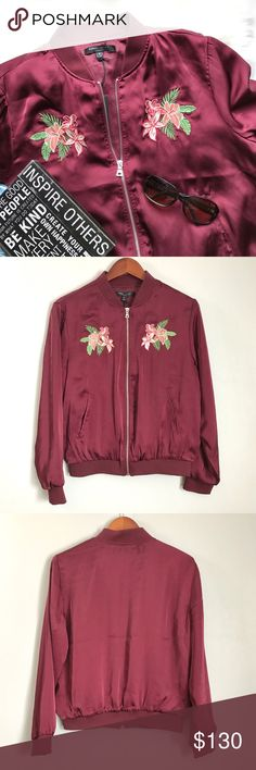 Romeo & Juliet Couture Bomber Jacket Shiny maroon bomber with trendy floral appliqué (lilies?). Stay fashionable and warm with you later with this hot tickets item. 3 itty bitty pulls (pictured). Hardly noticeable at all! Romeo & Juliet Couture Jackets & Coats