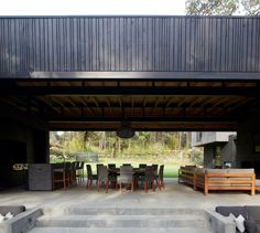 A charred-wood-clad volume extends perpendicular to the main house to create a roof over an exterior living room and dining room in this Mexican home. Outdoor Areas, Indoor Outdoor, Basement Floor Plans, Charred Wood, Journal Du Design, Dark House, Exposed Concrete, Ground Floor Plan, Roof Plan